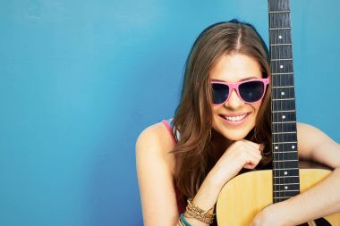 fashion music look with young model in sunglasses holding acoustic guitar on blue background
