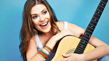 fashion music look with young model holding acoustic guitar on blue background