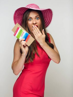 woman wearing big summer hat and red dress holding passport