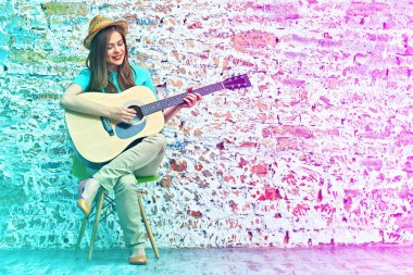Young woman sitting on chair play guitar.