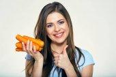 Fotografie Usměvavá mladá žena držící hromadu mrkve a ukazuje palcem nahoru, zdravé jídlo koncept