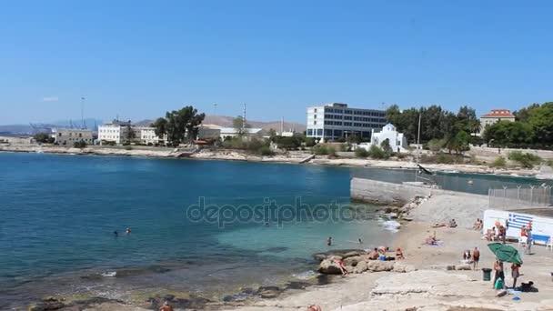 people on the beach at Saronic Gulf,  Piraeus Port in Attica, Greece