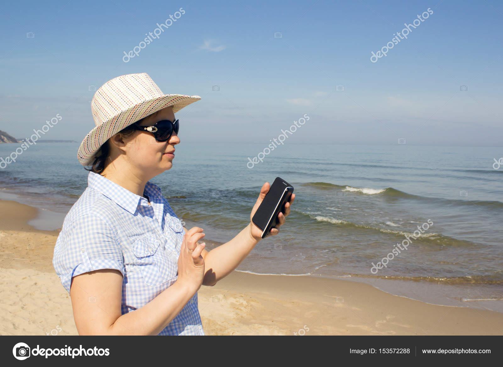 Ragazza Che Tiene Un Cellulare Con Sfondo Oceano Mare Foto Stock