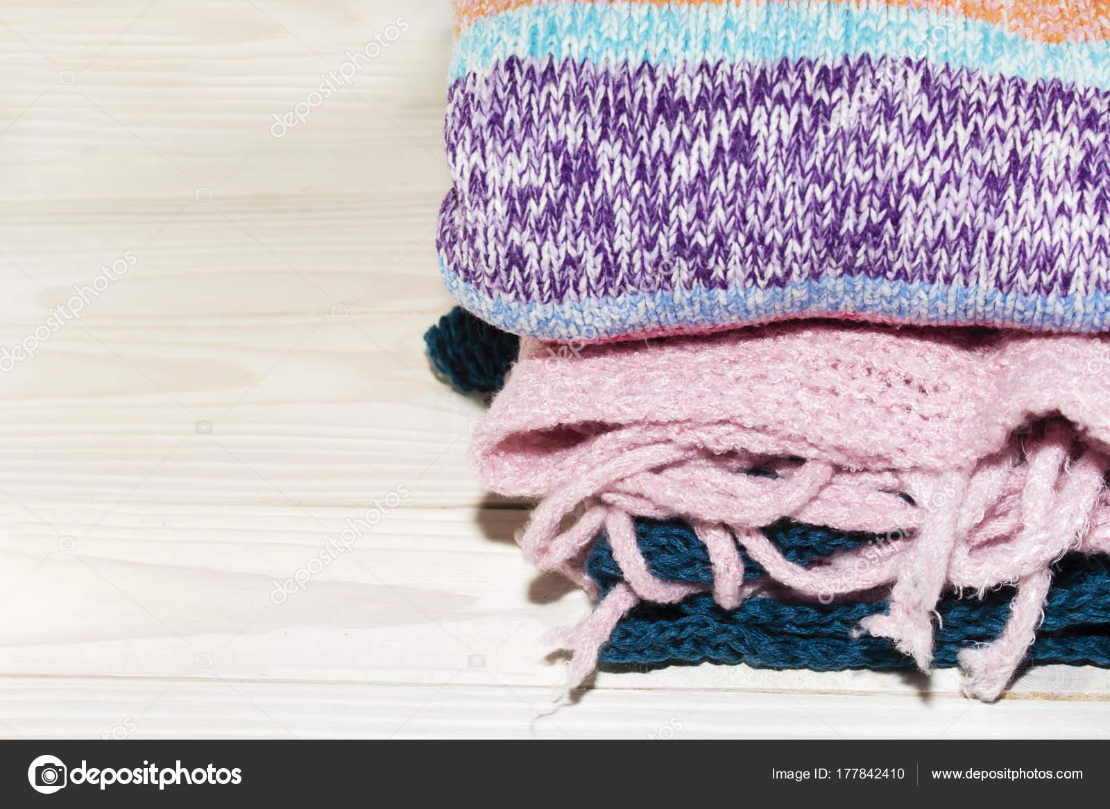 6281b5583141 Πουλόβερ πλεκτό μαλλί. Σωρός από πλεκτό χειμωνιάτικα ρούχα σε ξύλινο  υπόβαθρο