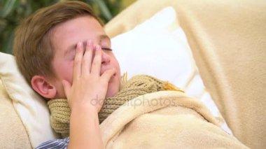 Beteg gyermek fiú fekszik az ágyban, a láz, pihenő, köhögés, és fúj az orrát