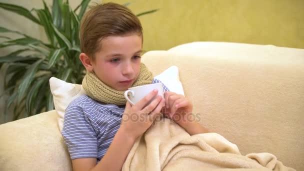 kranker Junge mit einer Tasse heißem Tee im Bett