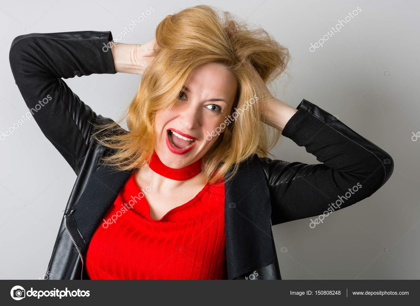 Ausdrucksstarke Frau in schwarzer Jacke gegen eine Wand