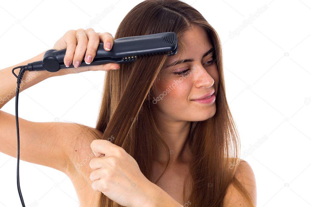 Giovane donna sorridente con capelli marroni lunghi con raddrizzatore dei capelli  su priorità bassa bianca in studio — Foto di Dmitroza 7847a234df62