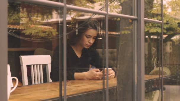 Mladá žena v kavárně pomocí mobilního telefonu