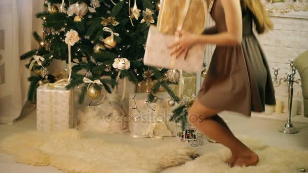 Gyönyörű nő bujkál a karácsonyfa alatt ajándékok