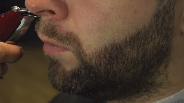 Shaving beard of man in barber shop