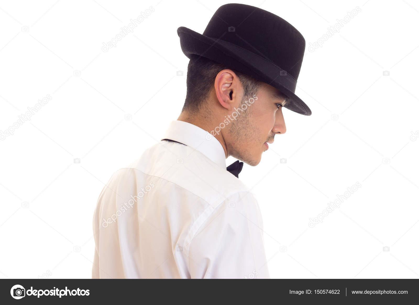 e816f3e644767 Beau jeune homme en chemise blanche avec un noeud-papillon noir et chapeau  noir sur fond blanc en studio — Image de ...