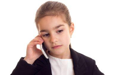 Little girl in black jacket talking on phone