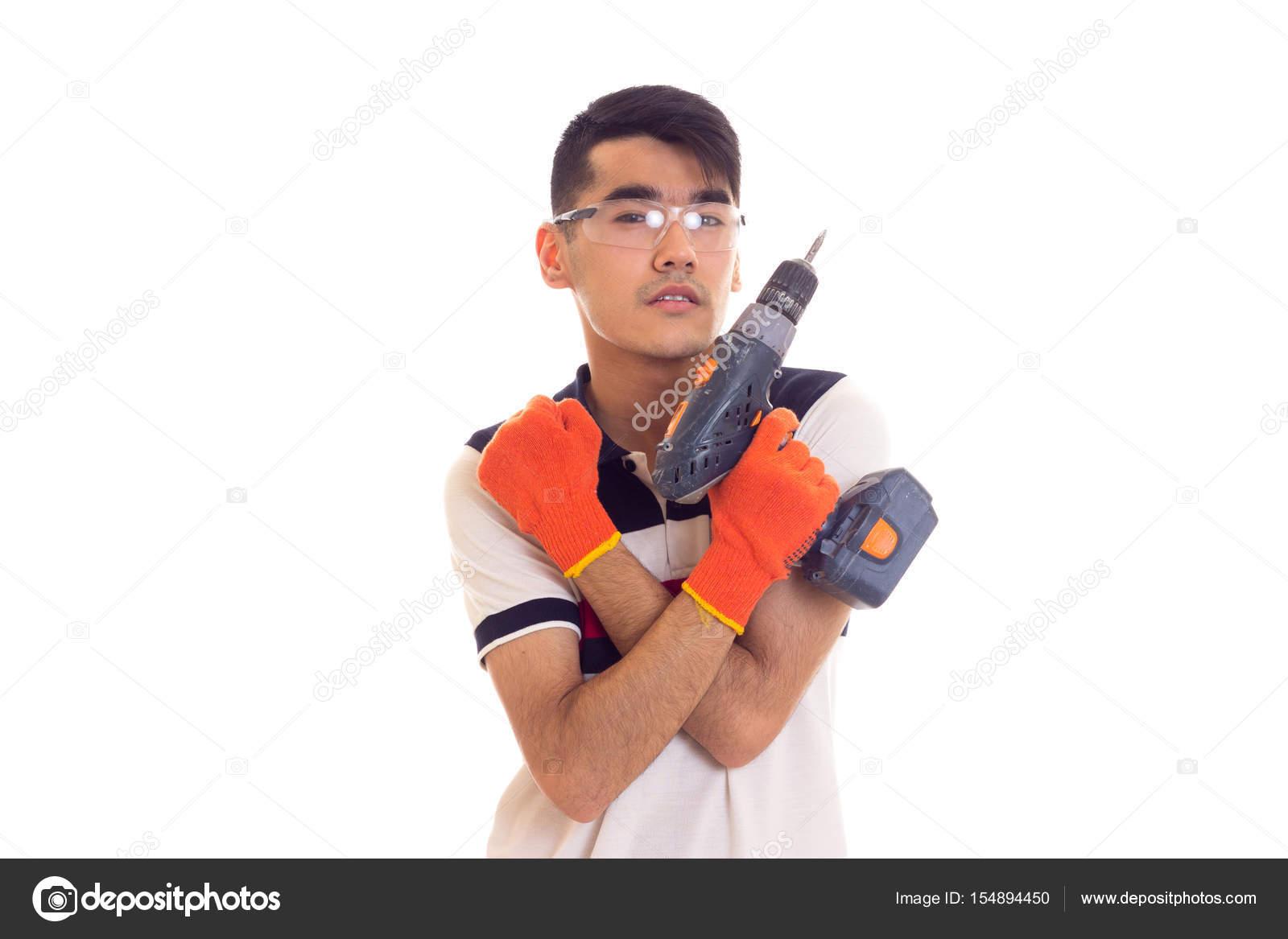 Jeune homme avec des gants et de lunettes tenant tournevis électrique —  Photo feee51b2c6a