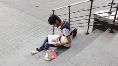 Portrait of a happy male asian student sitting on stairs and reading book