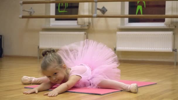 Little ballerina in pink dress doing choreography practice