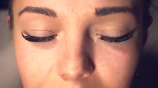 Žena s dlouhými řasami otevře oči a dívá se do kamery
