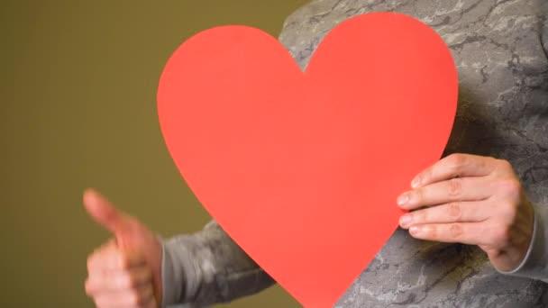 Muž drží velké červené srdce a ukazují palce nahoru