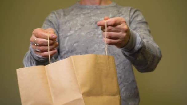 Man taking glass eco bottle with clear water from paper bag