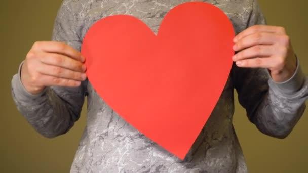 Muž držící velké červené srdce na hrudi