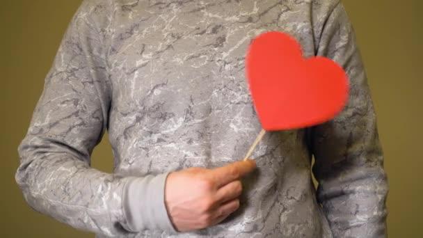 Muž s červeným papírovým srdcem v někom