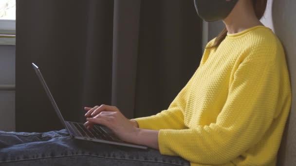 Nő maszkban dolgozik otthonról a laptopon