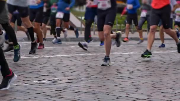 Men and women wearing sport shoes running the cobblestone road in city marathon. Slow motion shot