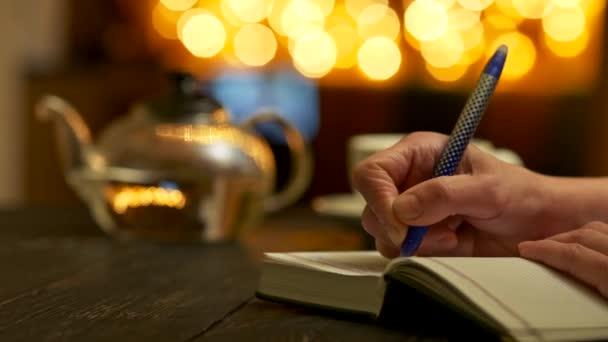 A nők kézzel írnak valamit a jegyzetfüzetébe. Teáskanna és sárga kerek bokeh a háttérben. Csúszó lövés Uhd