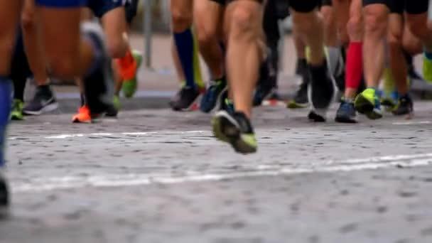 Men running in city marathon. Legs view. Slow motion shot