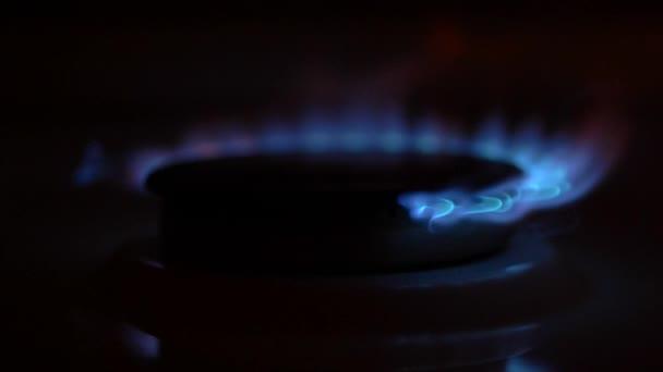 Gas schaltet sich ein, eine blaue Flamme steigt auf. Gasherd auf schwarzem Hintergrund