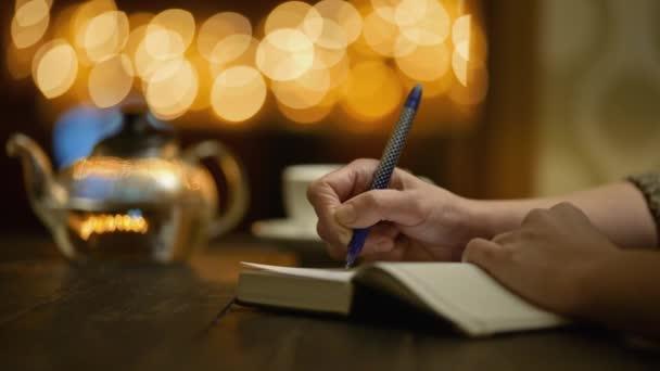 A nő naplót vezet, miközben egy hangulatos kávézóban ül egy csésze teával. A női kéz jegyzetfüzetbe ír.
