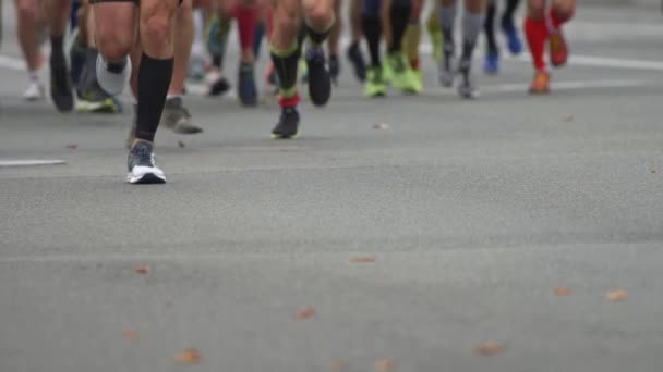 Unrecognizable Urban Marathon runners on the street. Slow motion close-up runners legs