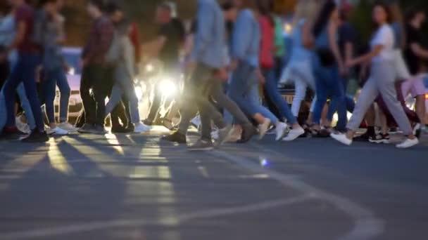 Unerkennbare Menschen drängen sich vor angehaltenen Autos über die Straße. Zeitlupenschuss