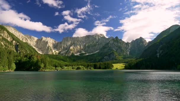 Water surface with ripples. Transparent turquoise colored alpine Fusine Lake, Italy in the bright sunny day. Dolomites mountains are seen in the background. Foothills are covered with forest. Cloudy