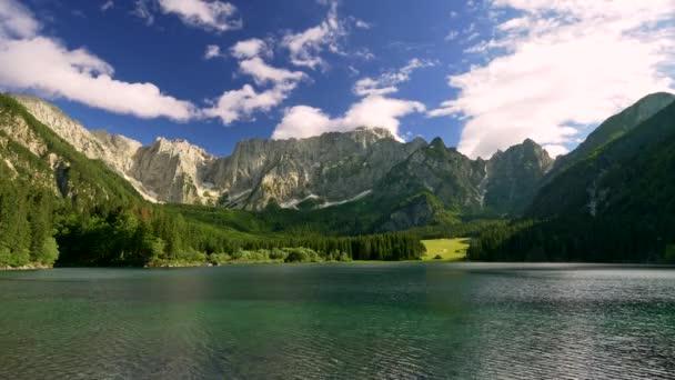 Povrch vody s vlnami. Průhledný tyrkysově zbarvený alpský Fusine Lake, Itálie v jasném slunečném dni. Dolomity jsou vidět v pozadí. Podhůří je pokryto lesem. Zataženo