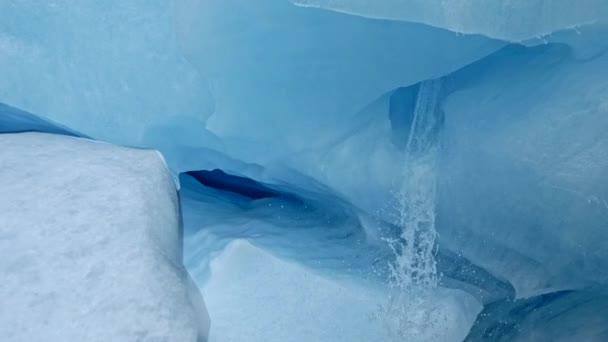 Vnitřek ledové jeskyně, která je bílý a modrý ledovec. Voda tekoucí rychle z tavícího ledu. Steadicam, 4k