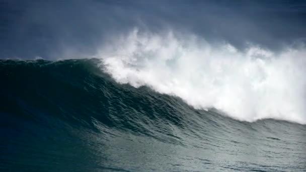 Hatalmas óceáni hullám gurul lassan és ütközik a part felé, sok fröccsenést okozva fehér habbal. Lassított felvétel.