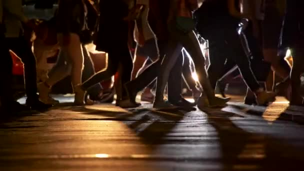 Menschenmassen überquerten den Fußgängerüberweg, während Autos hinter ihnen mit eingeschaltetem Licht anhielten und warteten. Abendliches Stadtleben. Zeitlupenschuss