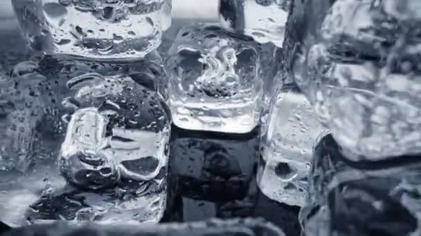 Geschmolzene Eiswürfel schließen sich an. Kamera bewegt sich durch Eiswürfel mit Wassertropfen vor dunklem Hintergrund. UHD, 4K