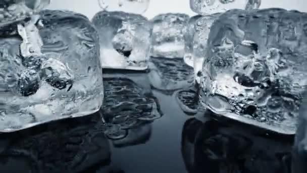 Eisschmelze. Kamera bewegt sich durch Eiswürfel und Wasserpfützen auf schwarzem Hintergrund. Extreme Hitze und Klimawandel