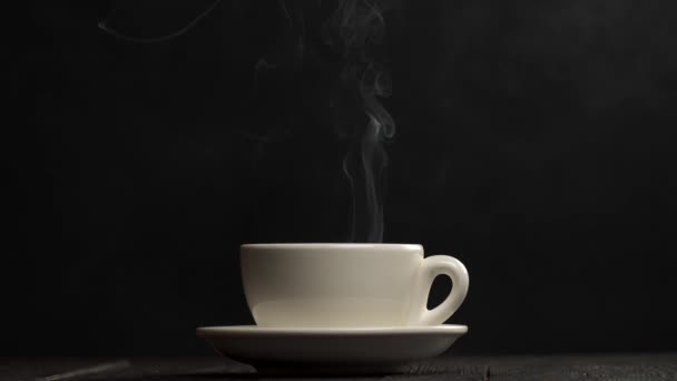 Cup of hot coffee against black background. Aroma spreads around the room. Slow motion shot