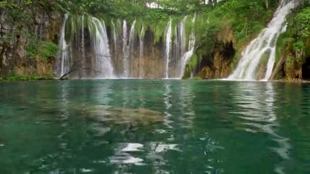 Tyrkysově zbarvené transparentní jezerní vody v národním parku Plitvická jezera, Chorvatsko. Vodopády a kaskády v pozadí. UHD