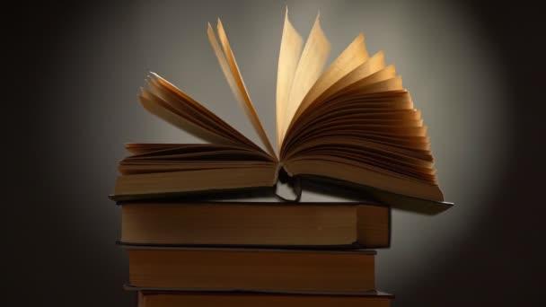 Zpomalený záběr knihy se pohupuje ve větru. Hromada knih na černém pozadí