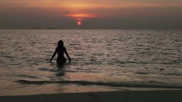 Sziluettjét a nő ellen a naplemente: ocean