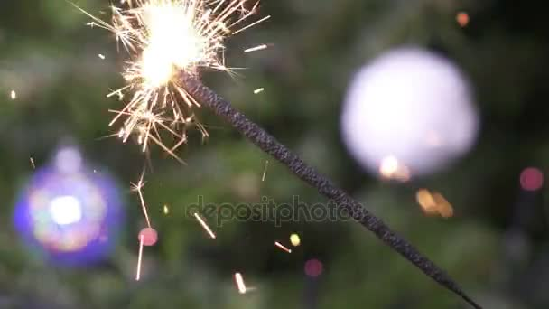 Bengal light against the background of a Christmas tree with New Years balls