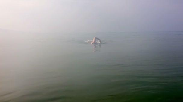 mladý sportovní muž plave v moři v mlze