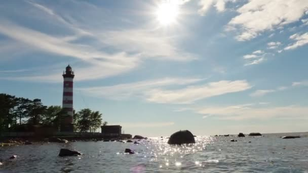 Wolken schweben am Sonnenhimmel über der Küste des Meeres mit einem Leuchtfeuer, Zeitraffer