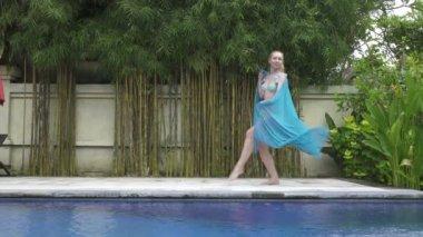 Young slender woman dances an oriental dance near pool in tropical resort