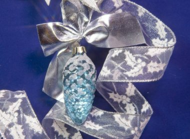 Beautiful  glass New Year's toy of an  cone, white brilliant tinsel on a blue background - New Year's composition, a card