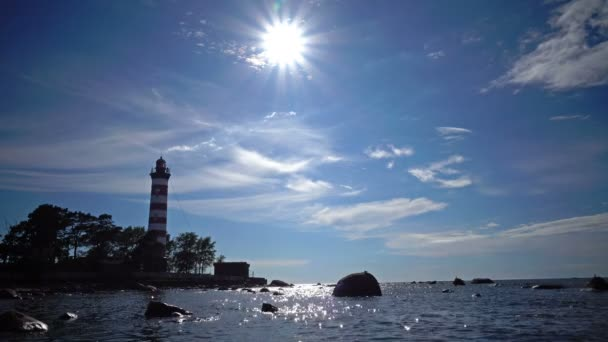 The building of the old beacon on the seashore against the background of the sky with brightly consecrating sun.Sunshine over a Lighthouse. St. Petersburg. Gulf of Finland